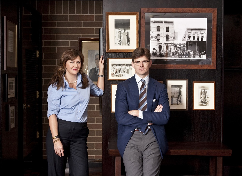 Kelly and David Hamilton standing in front of a wall of old photos