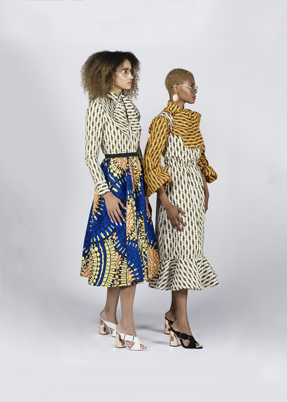 two women wearing ankara print dresses designed by rebuen reuel