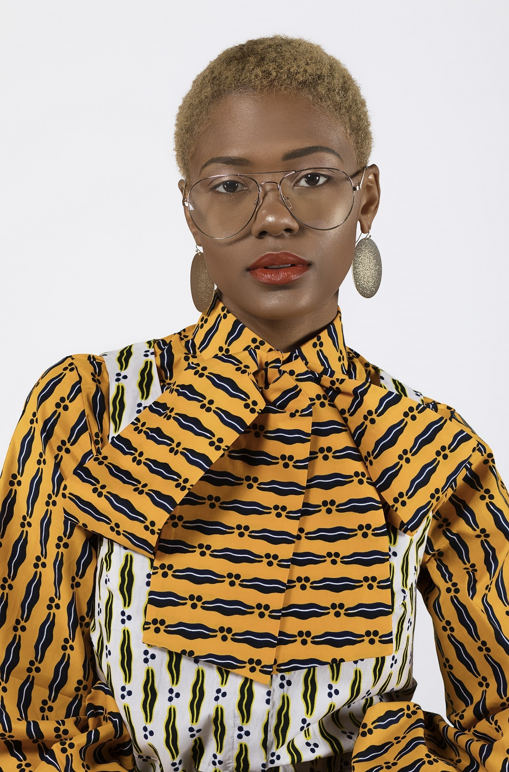 close up of a woman wearing glasses and an ankara print dress designed by Reuben Reuel