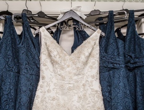 Navy bridesmaid dresses hung up with an ivory wedding gown