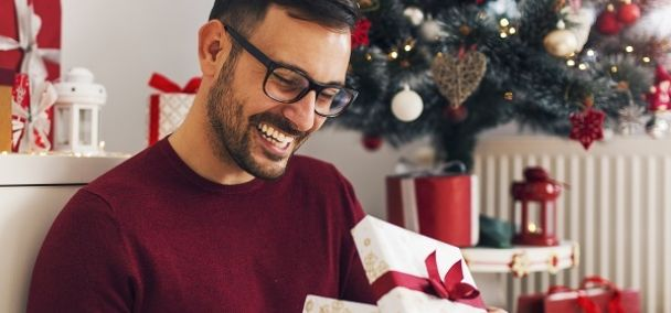 Man opening a holiday gift next to a Christmas tree