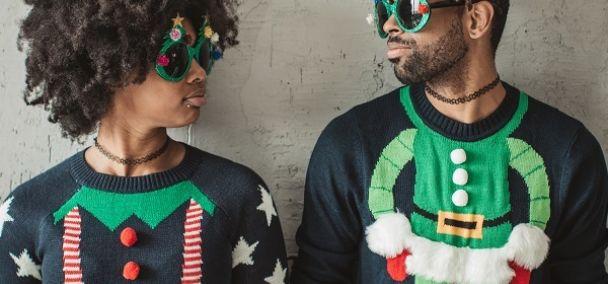 Two people wearing ugly Christmas sweaters with cotton balls
