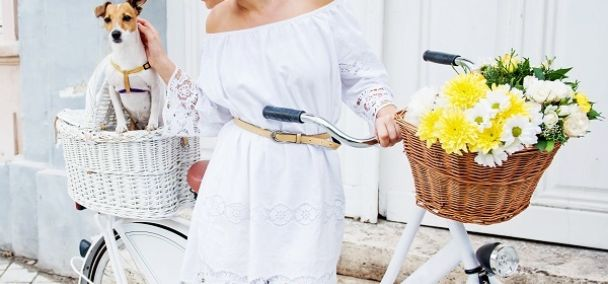 Woman wearing a white cotton off-the-shoulder dress riding a bicycle in town