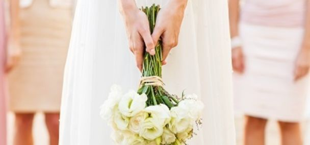 Bride holding bouquet with wedding guests wearing cotton dresses in the background