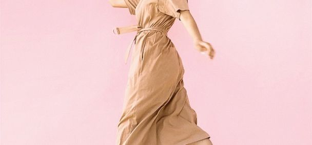 Woman jumping and wearing a neutral colored dress for spring