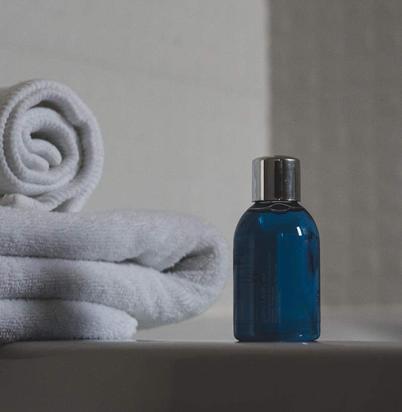 Blue glass bottle beside white towel 3872899